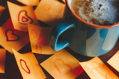 Coffee mug with hot coffee on the table surrounded with post it notes. Coffee mug with hot coffee on the table surrounded with post it love notes stock photos