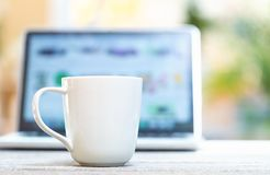 Coffee mug with laptop computer on a bright background royalty free stock images