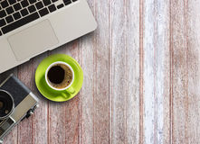 Coffee Mug, laptop computer and old camera on wooden Royalty Free Stock Images