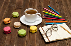 Coffee mug, macaroons, colored pencils and a notepad with glasses on a wooden background Stock Image