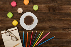 Coffee mug, macaroons, colored pencils and a notepad with glasses on a wooden background. Royalty Free Stock Photo