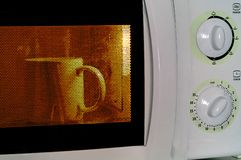 Coffee mug  in microwave oven Royalty Free Stock Image
