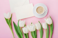 Coffee mug, paper card and spring tulip flowers for good morning on pink table above in flat lay style. Breakfast on Mothers day. Stock Photo