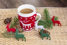 Winter Coffee in a Christmas Mug with Christmas Deers. Coffee mug with pine cones and deers.Christmas festivities Stock Image