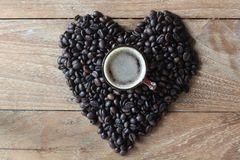 Coffee mug are placed on the heart shaped coffee beans. stock image