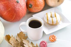 Coffee mug among the pumpkins, donut with icing, candy canes Royalty Free Stock Photos