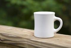 Coffee Mug on Railing. White ceramic coffee mug sitting on a wooden deck railing Royalty Free Stock Image
