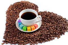 Coffee mug with rainbow colored sugar on beans Royalty Free Stock Photo