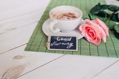 Coffee mug with rose nd notes good morning on white rustic table from above, cozy and tasty breakfast, vintage toned Stock Photography