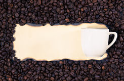 Coffee mug on a sheet of old paper on the background of coffee b Stock Image