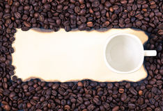 Coffee mug on a sheet of old paper on the background of coffee b Stock Photo
