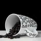 Coffee mug on side with coffee beans Stock Photography