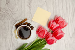 Coffee mug with spices, clean note, pink tulips on a wooden back.  Royalty Free Stock Image