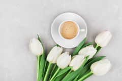 Coffee mug with spring flowers for good morning on gray stone table top view in flat lay style. Breakfast on Mothers or Womens day Stock Image