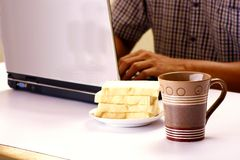 Coffee mug, stack of bread and man working on a laptop computer in the background Royalty Free Stock Photo