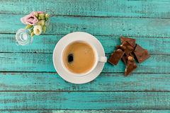 Coffee mug steam, chocolate and flowers in vase on table Royalty Free Stock Photography