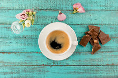 Coffee mug steam, chocolate and flowers in vase on table Stock Image
