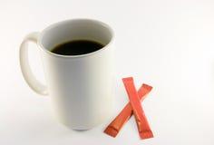 Coffee Mug and Sugar. Tall white coffee mug with two red sugar sachets on a white background Stock Image