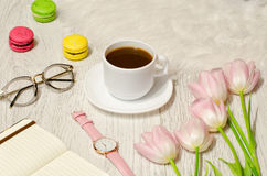 Coffee mug, sunglasses, watches, notebook and pink tulips on the table. Working concept. Top view Stock Photography
