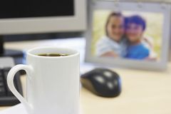 Coffee Mug On Table With Family Photo Royalty Free Stock Image