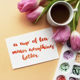 Coffee mug, watercolor palette, pink tulips on a peach background. Inspirational quote. A cup of tea makes everything better written in calligraphy style with royalty free stock images