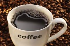 Coffee Mug. White coffee mug filled with black coffee on coffee bean background stock images