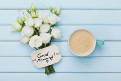 Coffee mug with white flowers and notes good morning on blue rustic table from above. Beautiful breakfast. Flat lay. Royalty Free Stock Photography