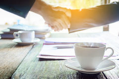 Coffee mug on a wooden desk and a businessman shaking hands Stock Images