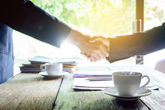 coffee mug on a wooden desk and a businessman shaking hands Royalty Free Stock Image