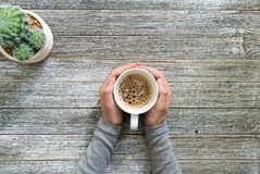 Coffee mug on a wooden desk. Person holding a coffee mug on a wooden desk overhead view stock photos