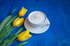 Coffee mug with yellow tulip flowers Stock Images
