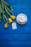 Coffee mug with yellow tulip flowers Royalty Free Stock Photos