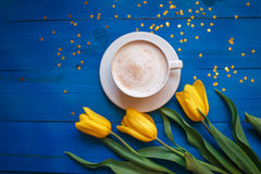 Coffee mug with yellow tulip flowers royalty free stock images