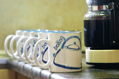 Coffee Mugs. Coffe mugs lined up next to coffee pot stock image