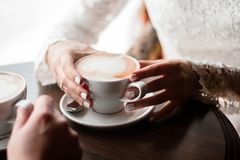 Coffee mugs of cappuccino in the hands of a loving couple. Coffee cappuccino royalty free stock photos