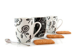 Coffee mugs with cookies. Black and white coffee mugs with cookies and spoons royalty free stock image