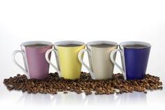 Coffee Mugs. Four coffee mugs in coffee beans stock image