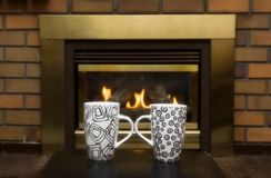 Coffee mugs in front of fireplace Stock Images