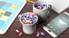 Coffee mugs full of pills, tablet, smartphone and notebook. On wooden desktop Stock Photo