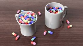 Coffee mugs full of pills Stock Photos