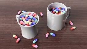 Coffee mugs full of pills Stock Photos