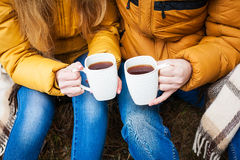 Coffee mugs iron in the hands of lovers. Stock Photography
