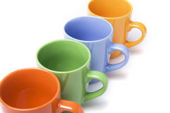 Coffee mugs line. With different colors over white royalty free stock images