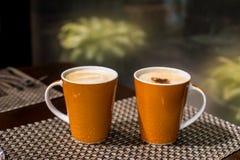 Coffee. 2 mugs of coffee on the mat Stock Photography