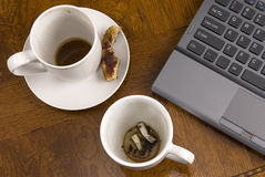 Coffee mugs and stress with laptop Royalty Free Stock Photo
