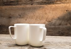 Coffee Mugs in Sunshine on Rustic Barn Wood Table. Close up detail of two large white coffee mugs shot against rustic brown barn wood background with ray of Stock Photos