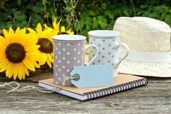 Coffee mugs. Two coffee mugs, sunflowers and straw hat stock photo