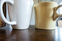 Coffee mugs on wood table. Upward angled view of two coffee mugs in natural light sitting on wood table - image stock photography
