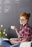Coffee is my passion!. Ginger woman wearing glasses, holding a white cup of coffee, blackboard coffee menu in the background Stock Photos