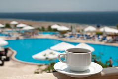 Coffee near sea. White cup of coffee near sea beach and pools Stock Photos